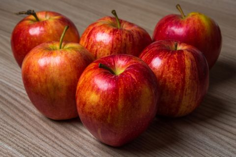 Fresh red apples on a wooden table