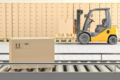 Cardboard boxes on conveyor belt.  There are forklift behind the conveyor belt.