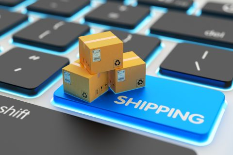 E-commerce, cardboard boxes on computer keyboard key closeup view